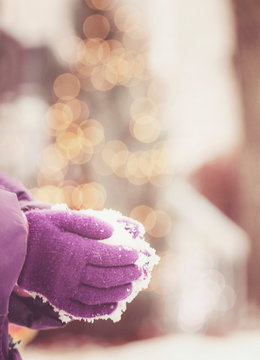 child holding fresh snow in her hands