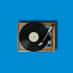 vintage turntable vinyl record player on blue background. retro sound technology to play music