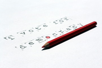 The word vote and democracy written with stamps and ink on white paper, and a red wooden pencil, concept image