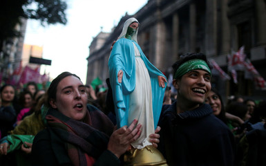 Activists hold an image of the Virgin Mary with a green handkerchiefs, which symbolizes the abortion rights movement, during a rally to legalize abortion, outside the National Congress in Buenos Aires