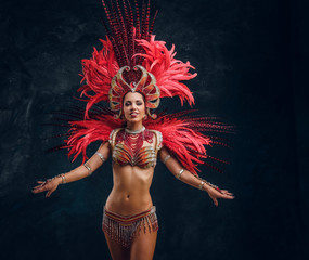 Happy beautiful brasil dancer in red feather costume is dancing on small scene.