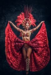 Talented joyful can can dancer in red feather costume is posing at small dark studio.