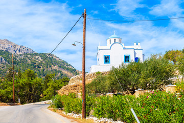 Fototapete - Typical white church on hill in mountain landscape of Karpathos island, Greece