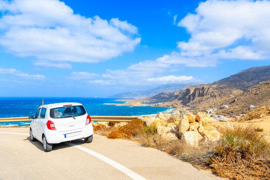 Rental car parked on road side during coastal drive around Karpathos island, Greece