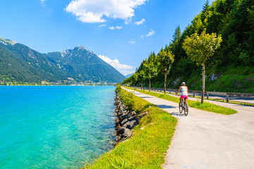 Young woman tourist riding bike along Achensee lake on sunny summer day, Pertisau, Tirol, Austria
