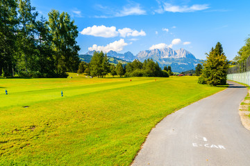 Fototapete - Way for electric cars on green golf course area against mountains background on sunny summer day, Kitzbuhel, Tyrol, Austria