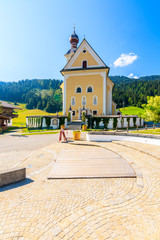 Wall Mural - Church on square in Going am Wilden Kaiser village on beautiful sunny summer day, Tirol, Austria
