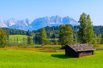 Wall Mural - Typical alpine old wooden hut on green meadow near Schwarzsee lake lake on sunny summer day, Tirol, Austria