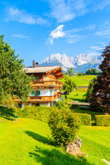 Wall Mural - Traditional alpine house in village of Going am Wilden Kaiser with Alps Mountains in background, Tirol, Austria