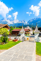 Fototapete - TIROL, AUSTRIA - JUL 30, 2018: Church cemetery and traditional alpine houses in village of Going am Wilden Kaiser on beautiful sunny summer day with Alps mountains in background, Tirol, Austria.