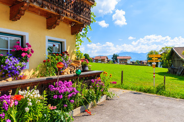 Wall Mural - Traditional alpine house decorated with flowers in village of Going am Wilden Kaiser on beautiful sunny summer day with Alps mountains in background, Tirol, Austria