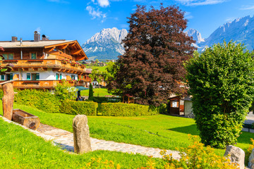 Fototapete - Traditional alpine house in village of Going am Wilden Kaiser with Alps Mountains in background, Tirol, Austria