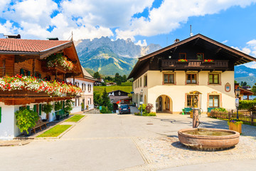 Wall Mural - Traditional alpine houses on square in village of Going am Wilden Kaiser on beautiful sunny summer day with Alps mountains in background, Tirol, Austria