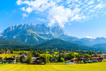 Wall Mural - Traditional alpine houses in village of Going am Wilden Kaiser on beautiful sunny summer day with Alps mountains in background, Tirol, Austria