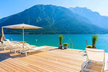 Pier with chairs on sunny terrace on shore of beautiful Achensee lake on sunny summer day with blue sky, Karwendel mountain range, Tirol, Austria