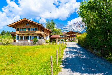 Wall Mural - Road and traditional alpine houses in village of Going am Wilden Kaiser on beautiful sunny summer day with Alps mountains in background, Tirol, Austria