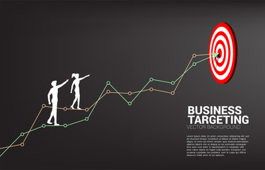 silhouette of businessman and businesswoman point to dartboard on line graph to center of dartboard. Business Concept of targeting and customer.route to success.
