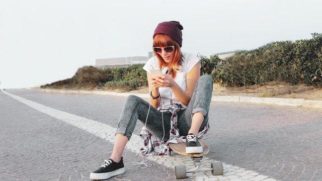 cute skater girl sitting on long board checking smart phone listening to music using internet.