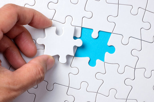 Hand placing the last jigsaw puzzle piece or holding missing jigsaw puzzle piece down in to the place