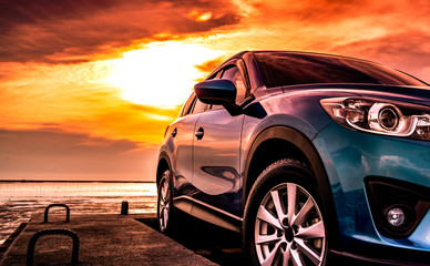 Blue SUV car with sport and modern design parked on concrete road at sunset sea beach with orange sky. Hybrid and electric car technology concept. Automotive industry. Car care service wallpaper.