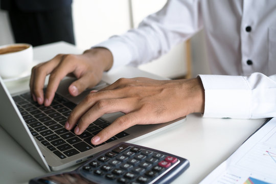 The human hand uses the keyboard by the notebook on the desk. Internet education and communication concepts