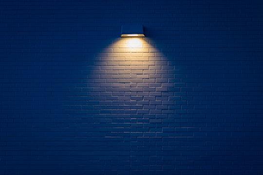 Single light illuminating a brick wall
