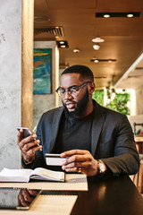 Hard work does pay off. Shot of african american businessman holding mobile and credit card, while resting in the cafe