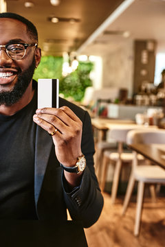 Price is what you pay. Value is what you get. Smiling african american businessman holds his credit card, looking at the camera while standing in the cafe