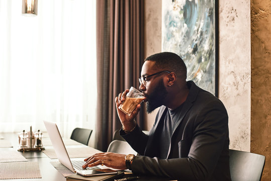 Be thankful for what you have. Work hard for what you don t have. African american businessman is working, using his laptop while drinking coffee in the cafe. Side view