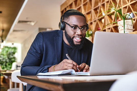 Just start. Young businessman with headphones sitting in cafe in front of laptop and networking