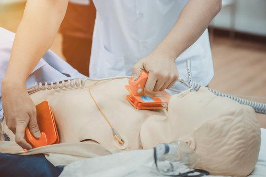 hands of doctor holding defibrillator electrods, performing defibrillation or electropulse therap