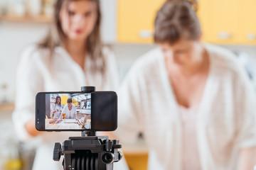 Cooking vlog. Women baking pastry biscuit cookies recording smartphone video tutorial. Media content creating equipment