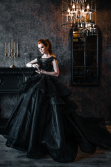 Attractive woman in black dress in medieval interior