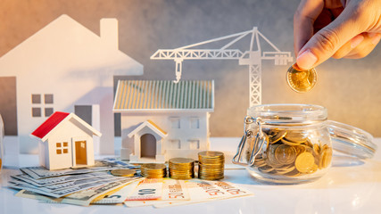 Real estate or property development. Construction business investment. Home mortgage loan rate. Hand putting coin in currency glass jar with Coin stack, banknotes, house and crane models on the table.