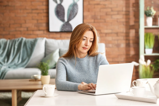 Portrait of mature woman working on laptop at home