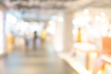 Abstract blur shopping mall corridor. Blurred retail and hall interior in department store. Defocused bokeh effect background or backdrop for business concept.