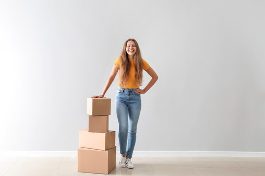 Young woman with cardboard boxes near light wall