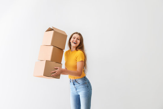 Young woman with cardboard boxes on light background