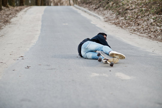 Fail falling from a skateboard. Street style arab man in eyeglasses with longboard longboarding down the road.