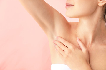 Beautiful young woman after laser hair removal procedure on color background