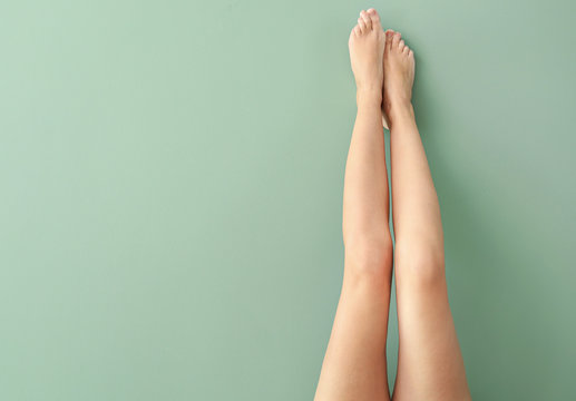 Beautiful young woman after laser hair removal procedure of legs on color background