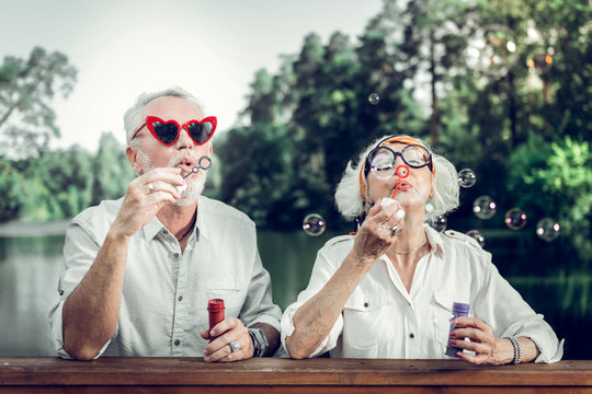 Happy couple in funny sunglasses blowing bubbles outdoors