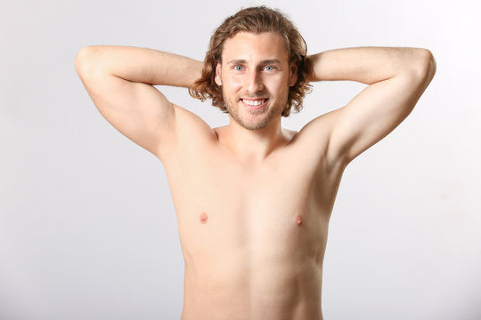 Naked young man after epilation on light background
