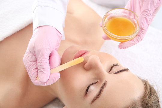 Beautician removing hair above upper lip of young woman in salon