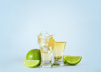 Shots of tequila with splashes on light background