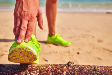 Sportsman stretching on a tropical sandy beach.