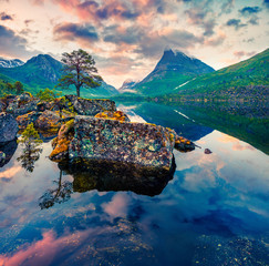 Impressive summer sunrise on the Innerdalsvatna lake. Colorful morning scene in Norway, Europe. Beauty of nature concept background. Artistic style post processed photo.