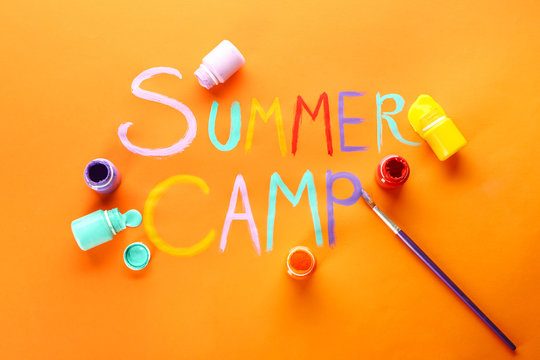 Words SUMMER CAMP, paints and brush on color background