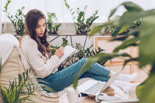 selective focus of attentive young woman writing using laptop and writing in notebook while sitting near green plants at home