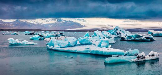 Arctic ducks between blue icebergs in Jokulsarlon glacial lagoon. Colorful sunset in Vatnajokull National Park, southeast Iceland, Europe. Beauty of nature concept background. Fototapete